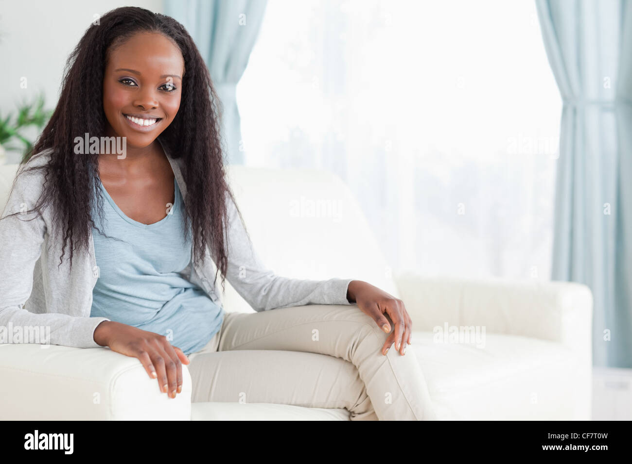 Woman sitting on sofa with legs folded - Stock Image