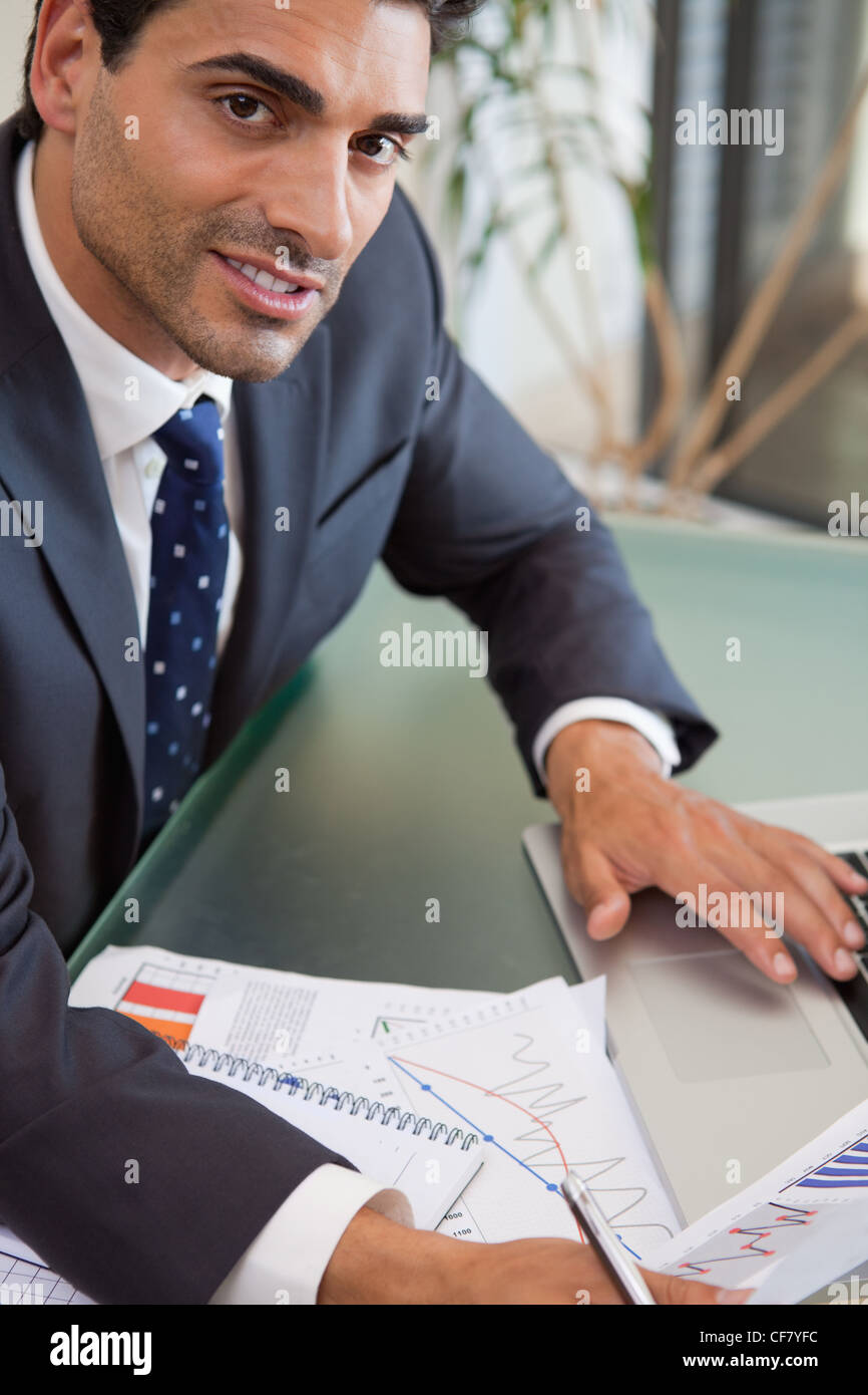Portrait of a focused sales person studying statistics - Stock Image