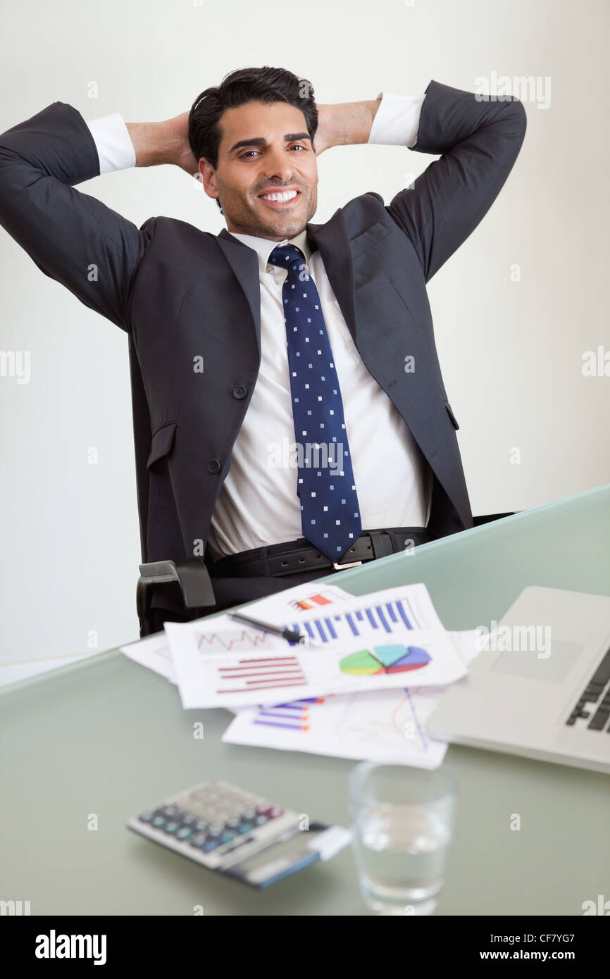 Portrait of a smiling sales person relaxing - Stock Image