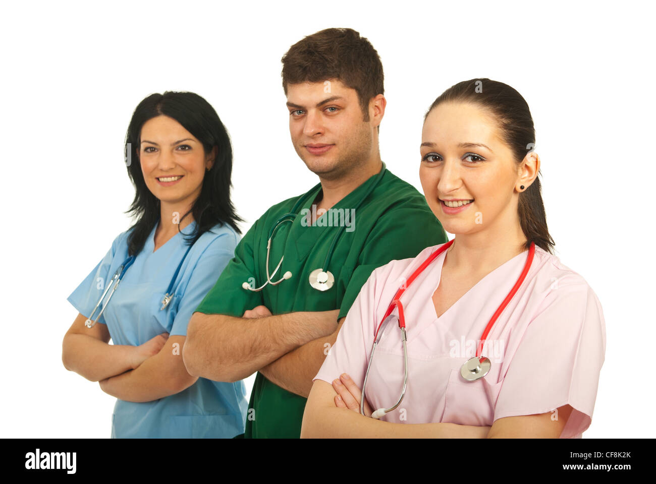 Happy three hospital workers standing in a line with arms folded isolated on white background - Stock Image