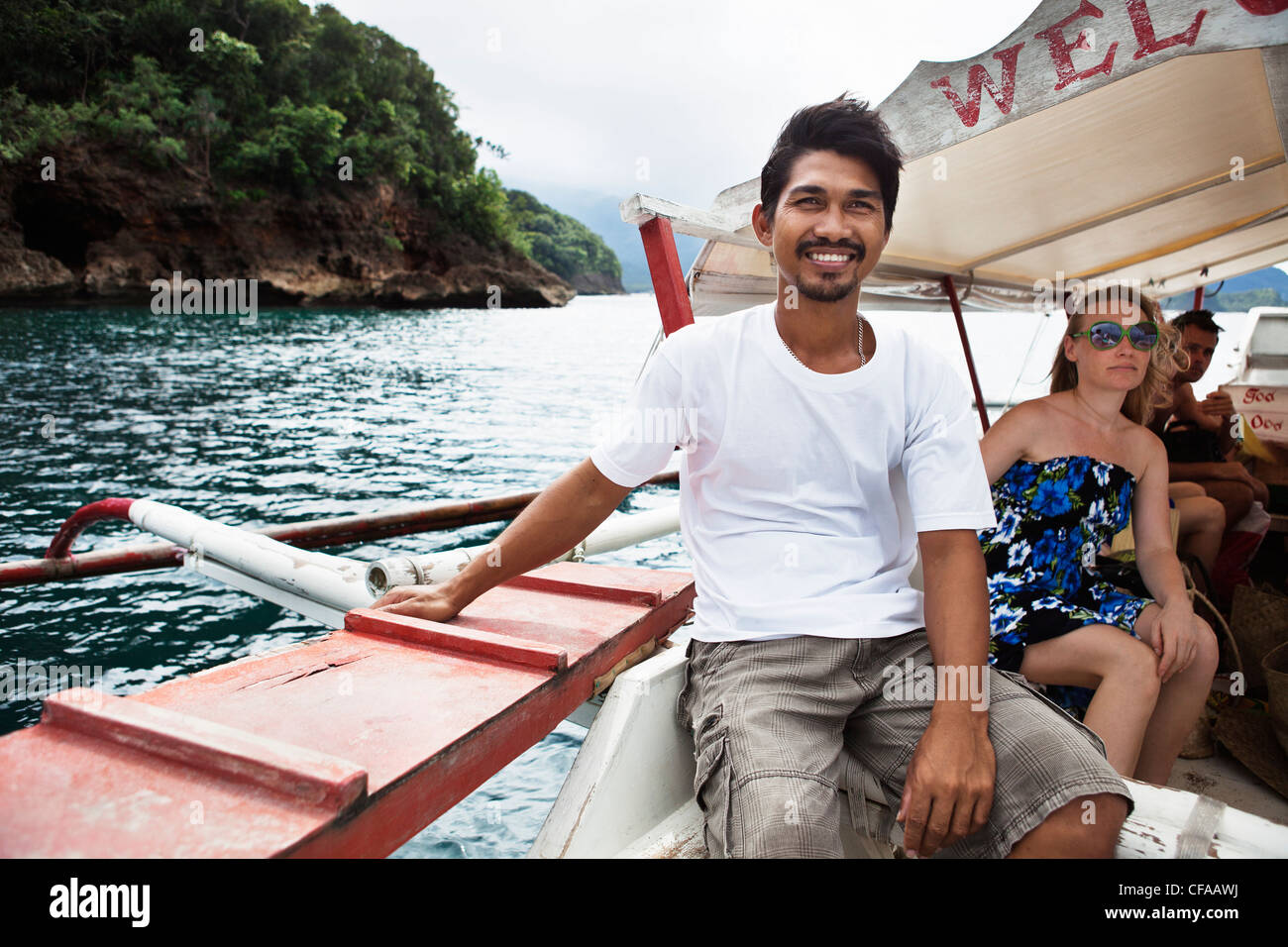 Man on tour boat in tropical waters - Stock Image