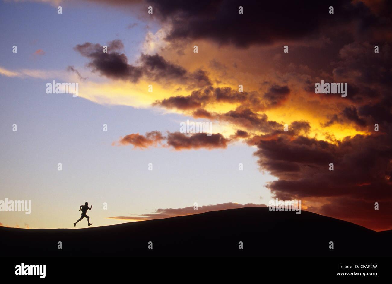silhouette woman running ridge distance towards - Stock Image