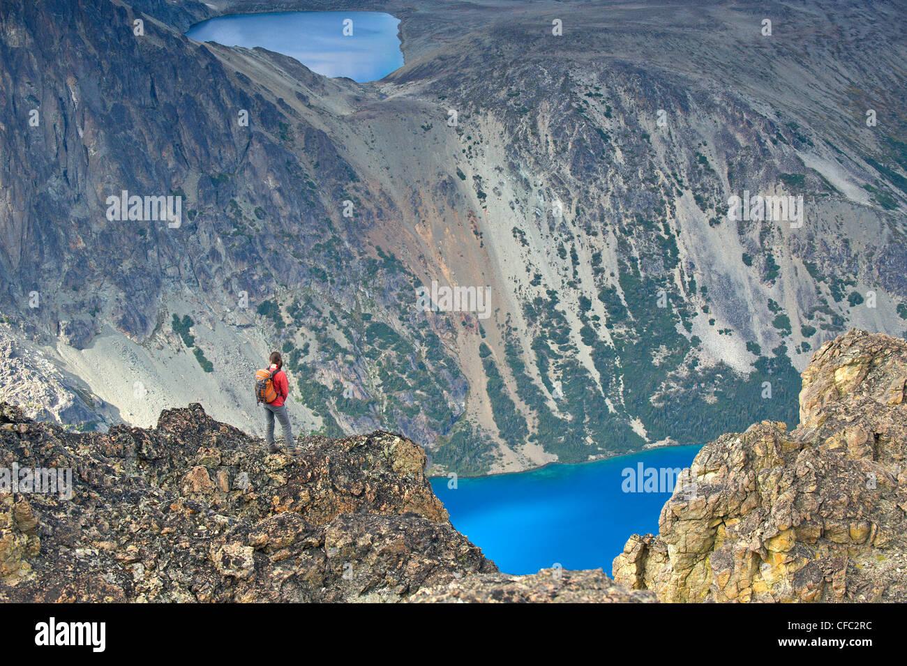 A woman surveys incredible alpine lakes in the Niut Range of British Columbia's Coast Mountains - Stock Image