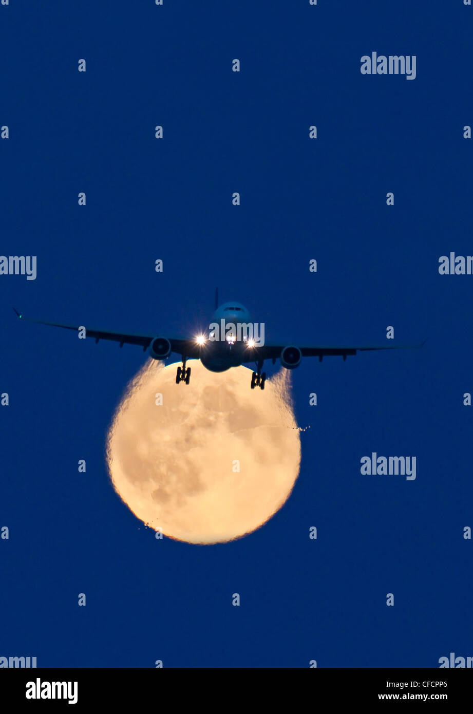 Airbus 330 passing full moon approach Vancouver - Stock Image