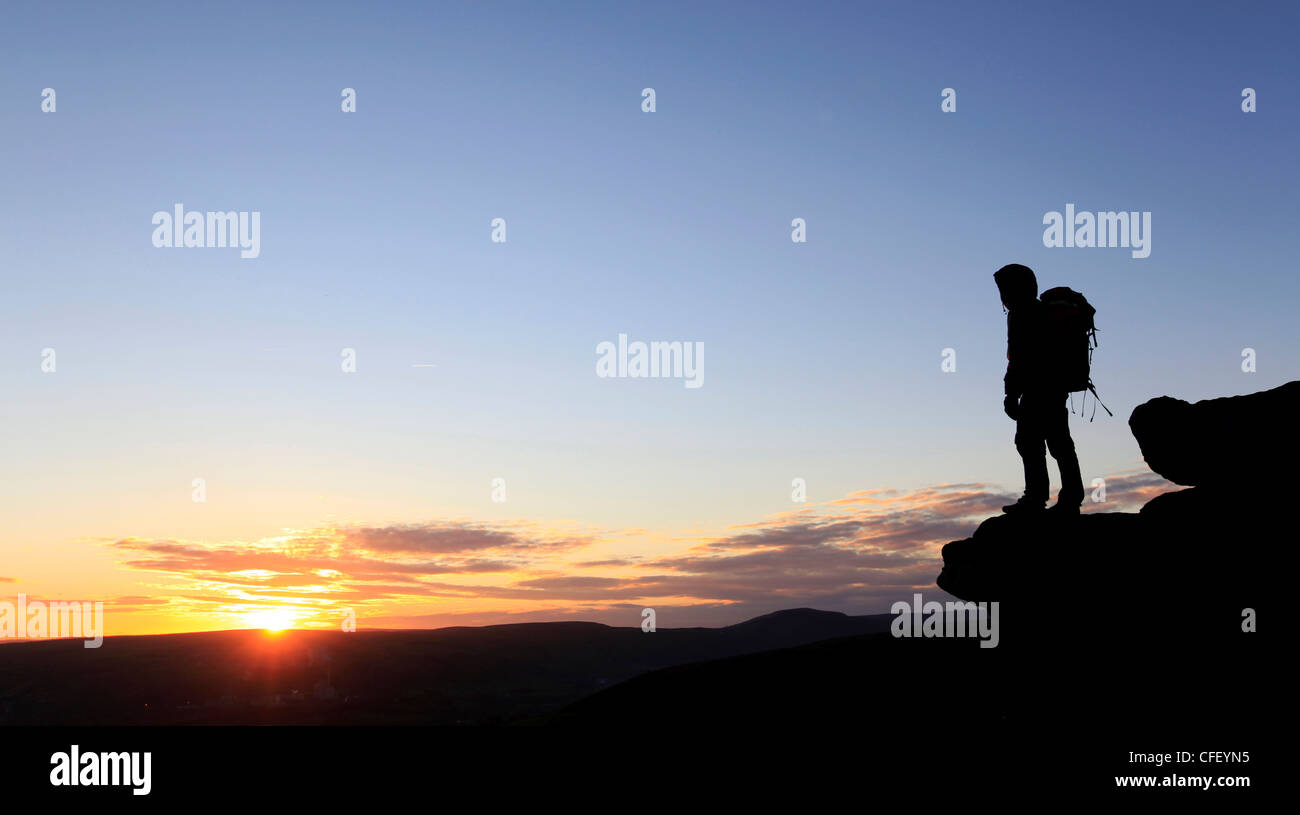 A hiker at sunset on Bamford Edge, near Edale, Peak District, Derbyshire, England, United Kingdom, Europe - Stock Image