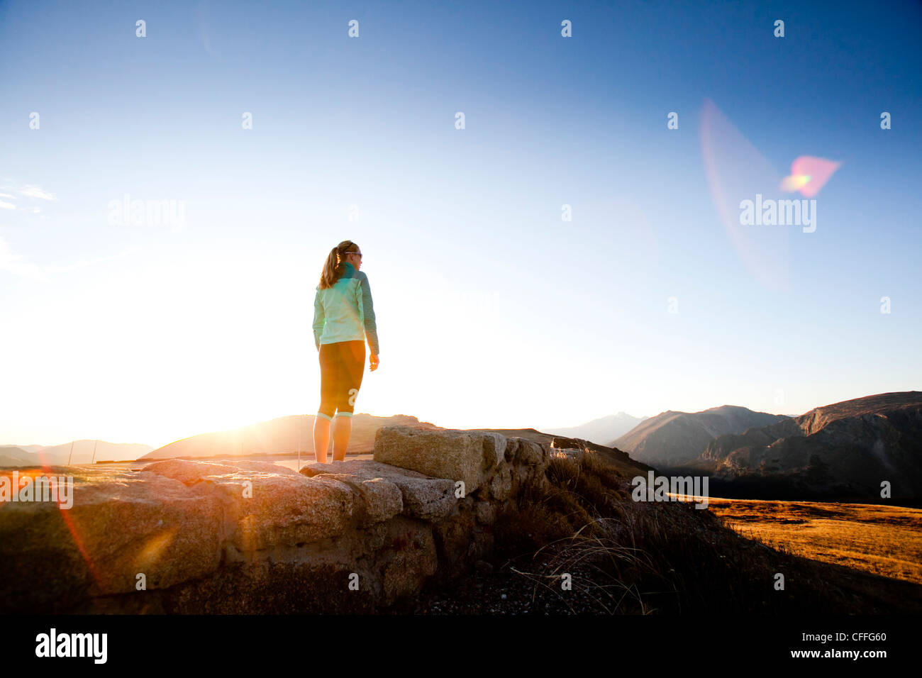 An athletic woman  runs along Trail Ridge Road (12,183 feet) near its apex at sunrise, Rocky Mountain National Park, - Stock Image