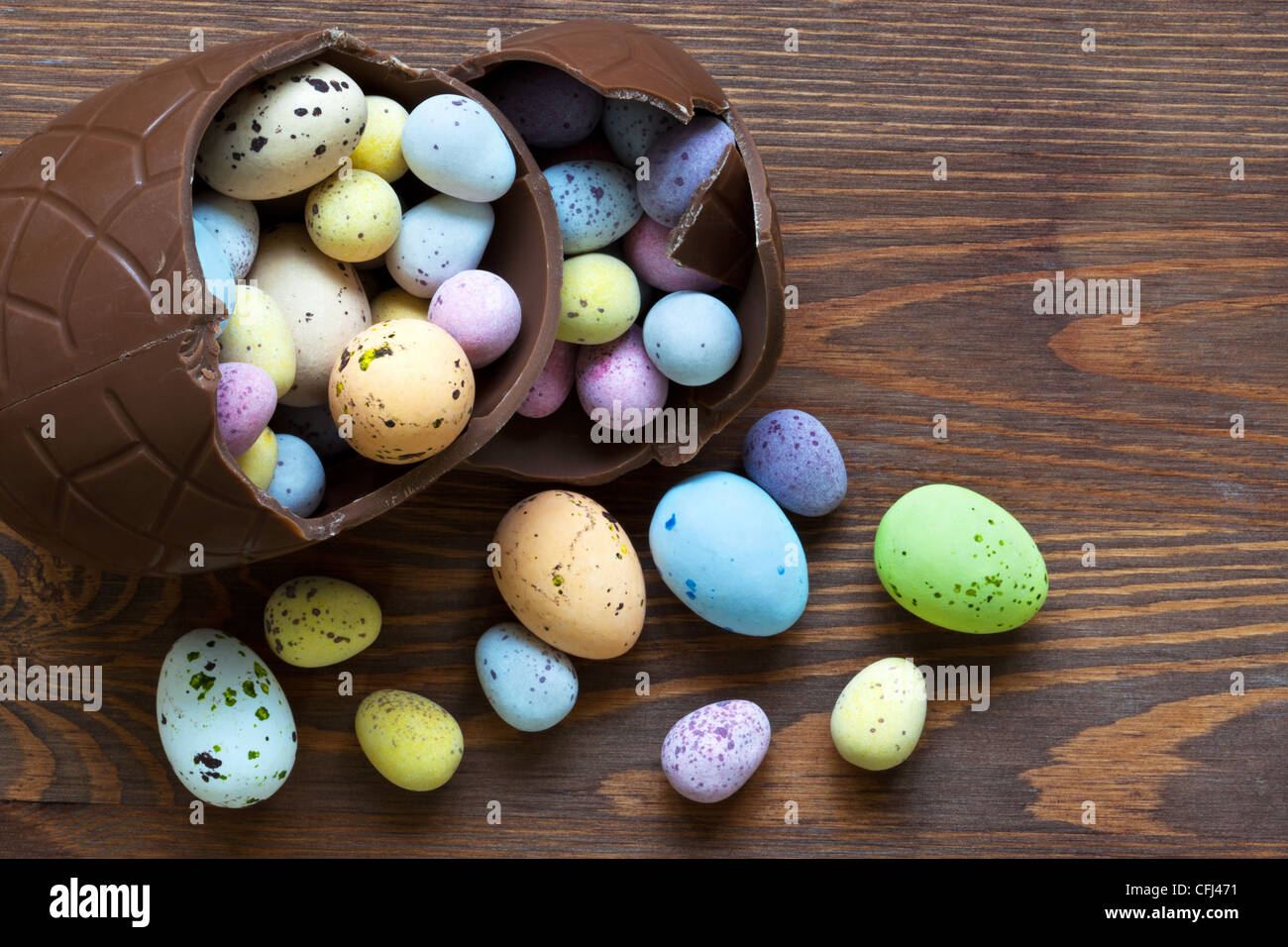 Still life photo of a large broken chocolate easter egg full of mini candy covered eggs in various pastel colours. Stock Photo