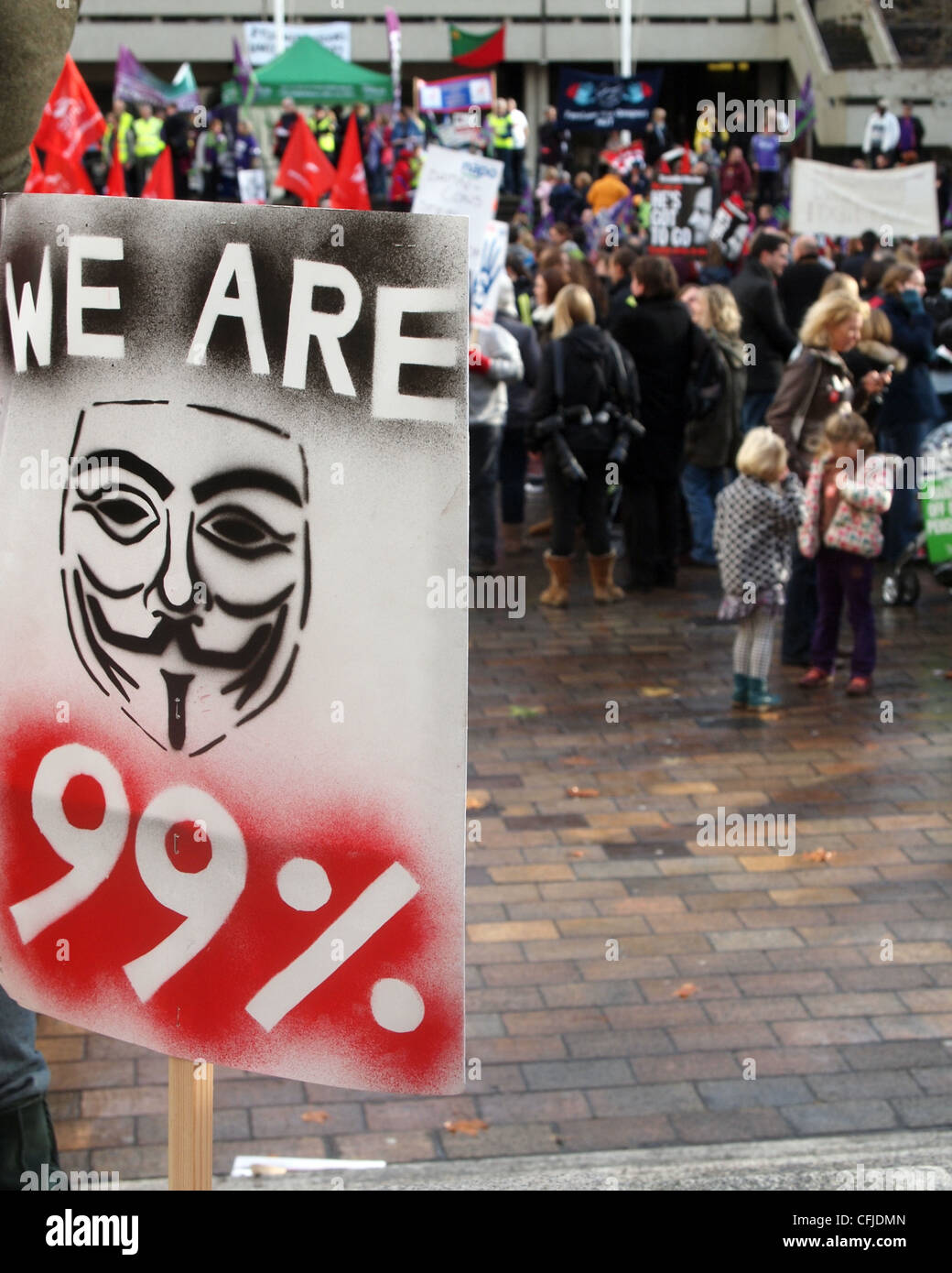 we-are-99-placard-with-the-guy-fawkes-mask-symbol-and-protesters-in-CFJDMN.jpg