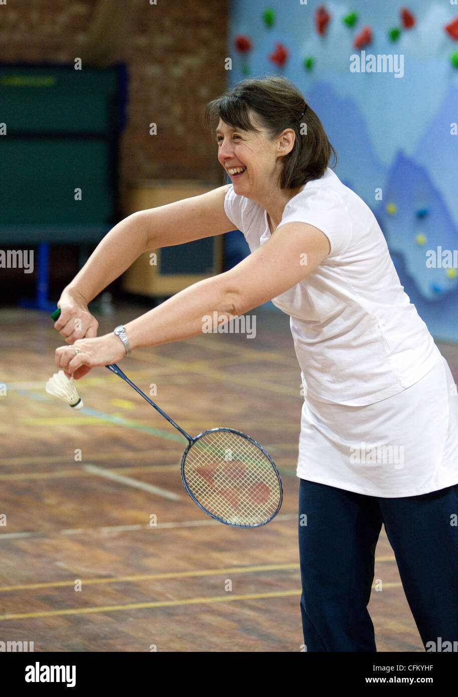 A middle aged lady badminton player serving, Newmarket Suffolk UK - Stock Image