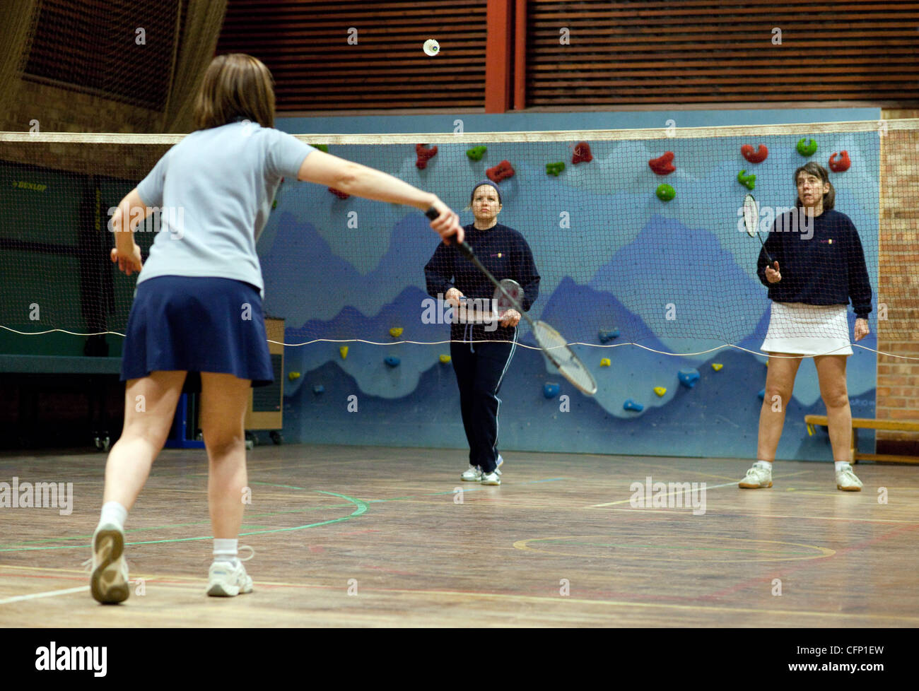 Three women playing a game of badminton, Newmarket Suffolk UK - Stock Image