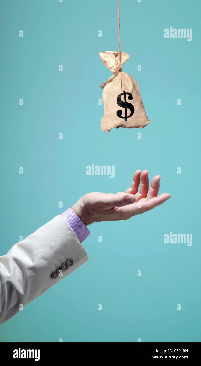 man's hand reaching for money bag - Stock Image