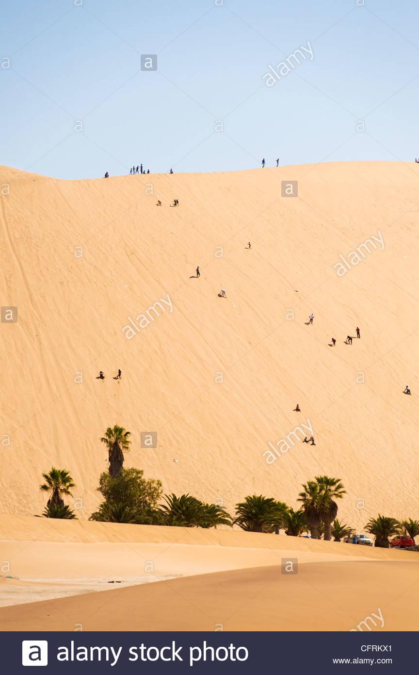 Tourists climb Dune 45, near Swakopmund, Namibia. - Stock Image