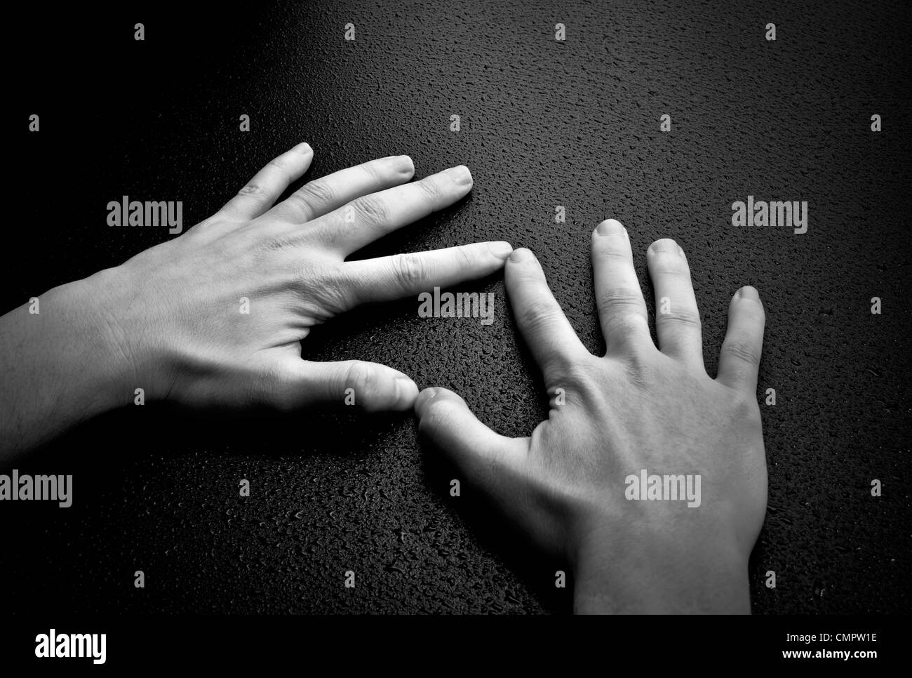 Two hands creating a heart shape on wet wood background - Stock Image