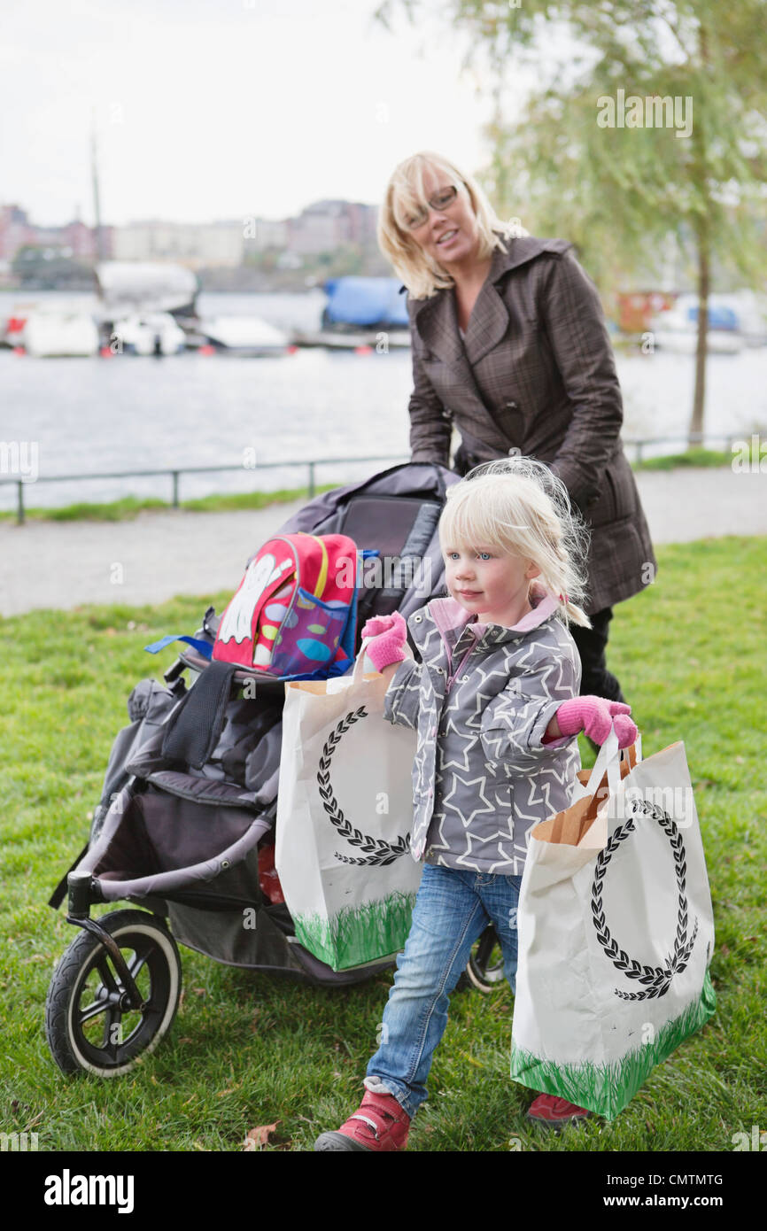 Child carrying bags while woman pushing cart - Stock Image