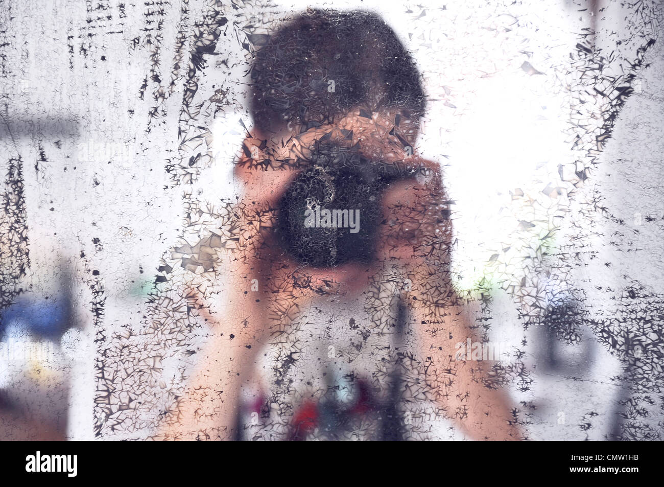 Photographer taking photograph of dirty mirror - Stock Image