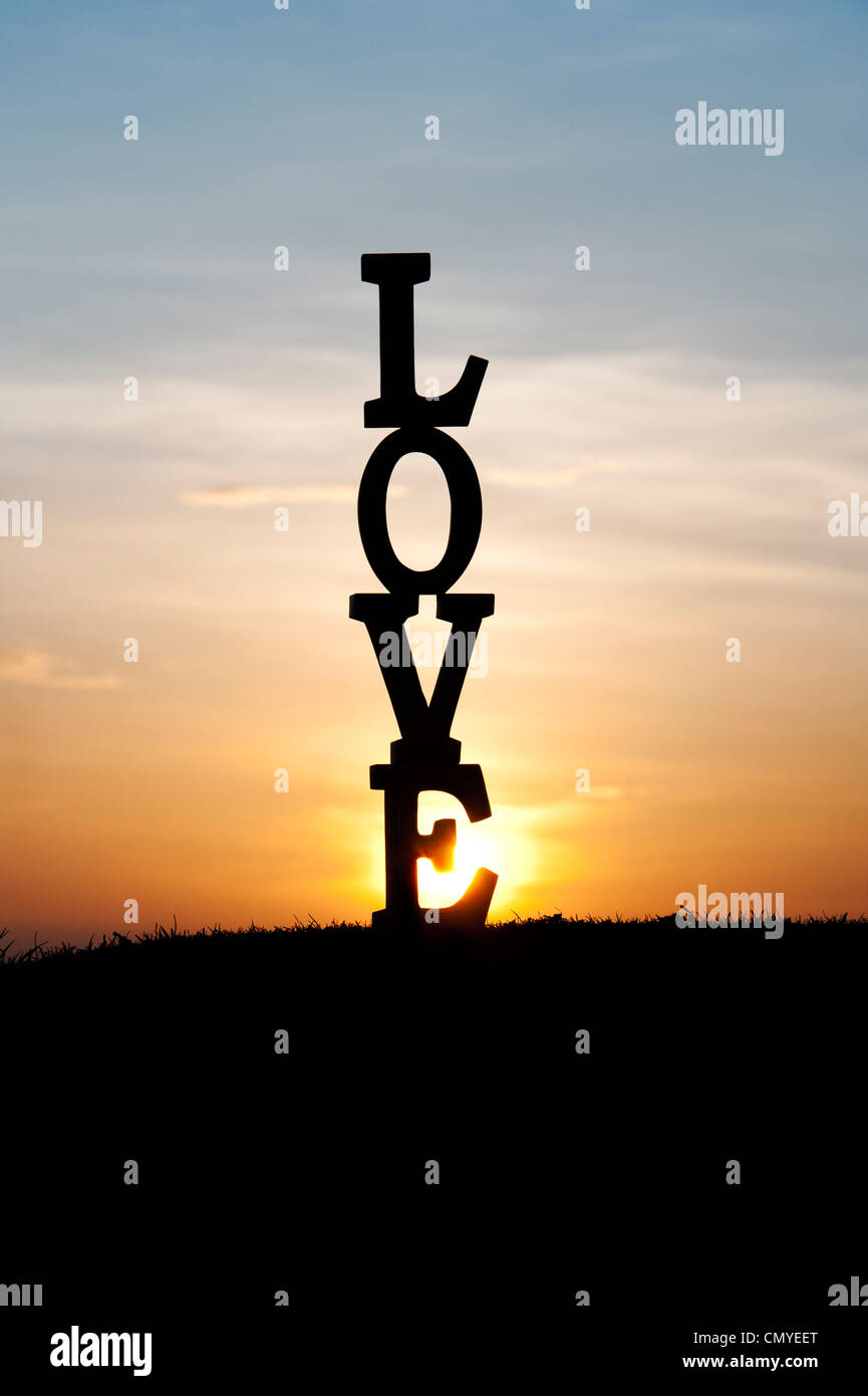 LOVE letters silhouette at sunset - Stock Image