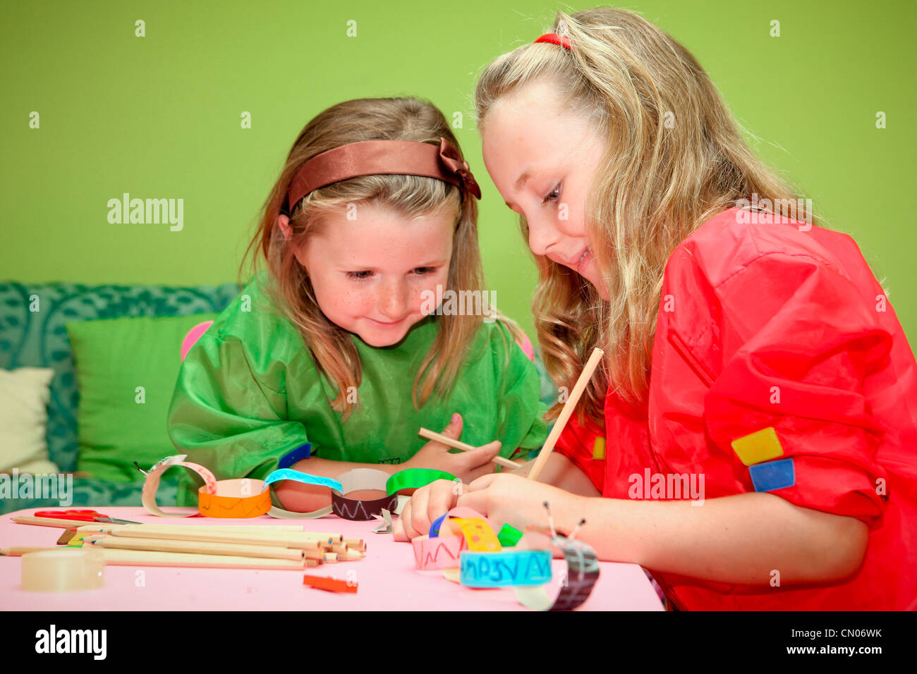happy smiling children playing drawing and making craft in class at kindergarten school - Stock Image