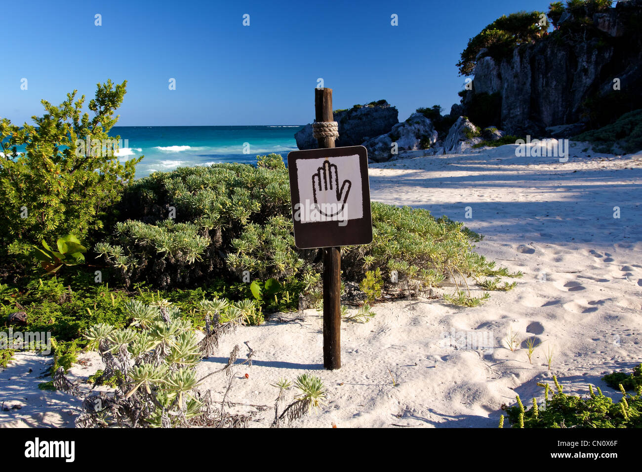 Brown and tan sign showing a hand pictogram at a beautiful Caribbean beach (landscape format) - Stock Image