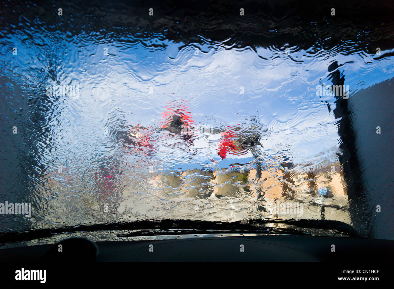View through the windshield of an automobile in an automated car wash. - Stock Image