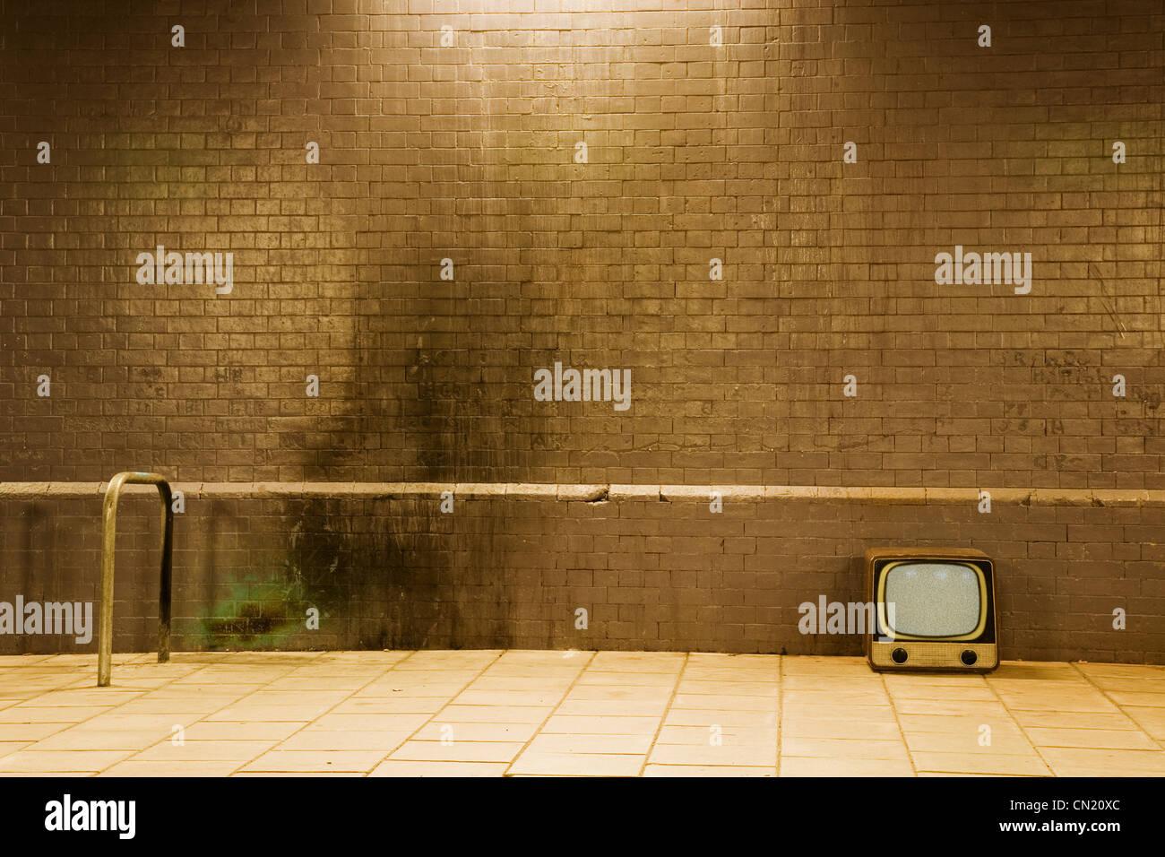Retro television by brick wall - Stock Image