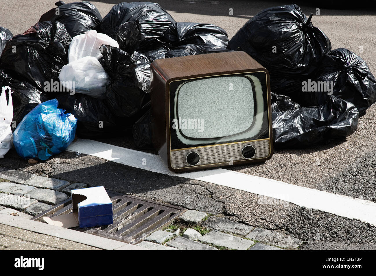 Retro television with pile of rubbish bags - Stock Image