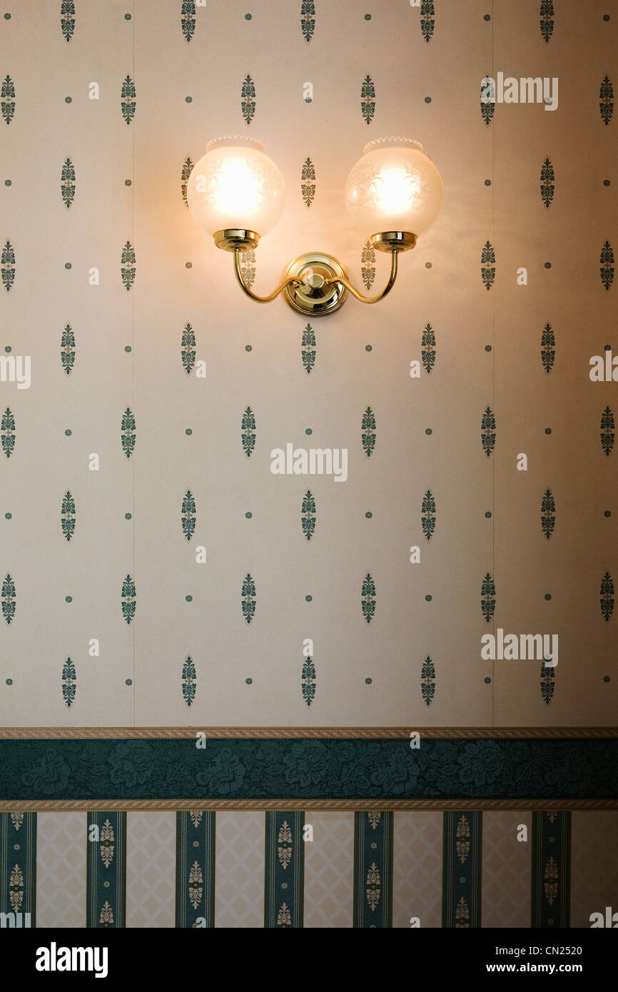 Wall lamp against patterned wallpaper - Stock Image