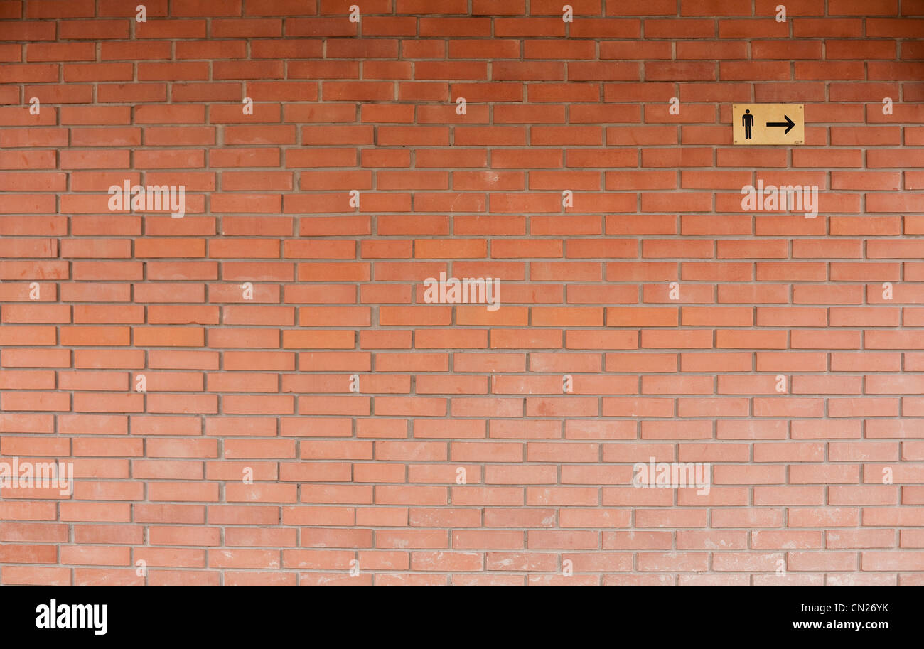 Male toilet sign on brick wall - Stock Image