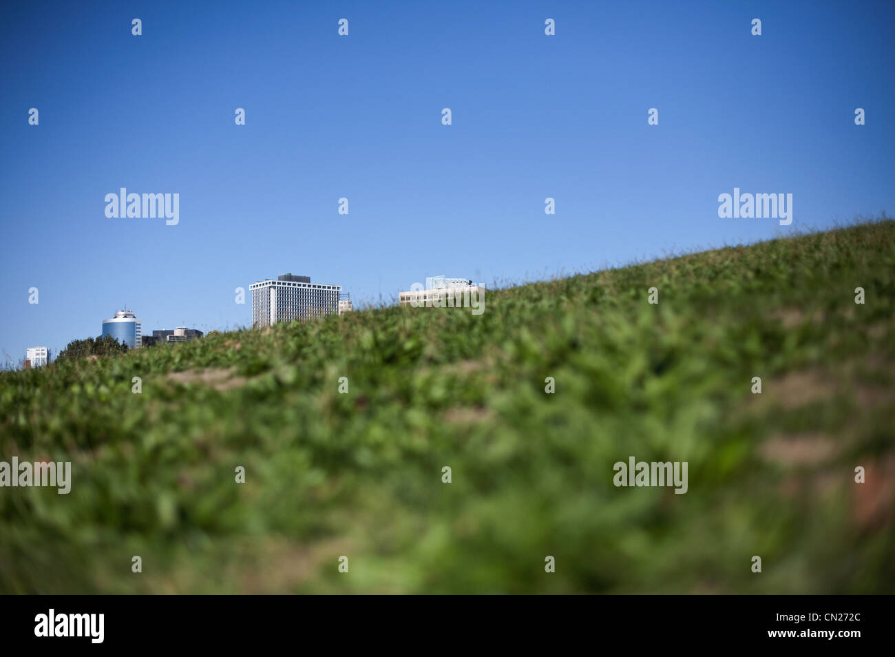 Buildings behind grassy hill - Stock Image