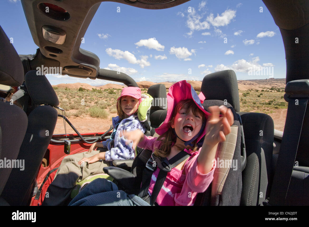 Two Young Girls Smiling in Backseat of Jeep, Moab, Utah, USA - Stock Image