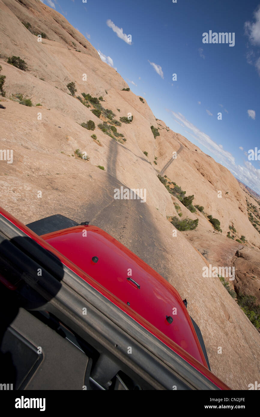View of Remote Road Across Red Rocks Through Jeep Sunroof, Moab, Utah, USA - Stock Image