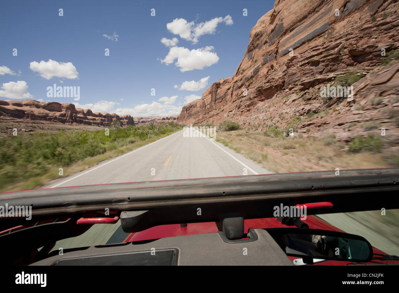View of Remote Highway Across Red Rocks Through Jeep Sunroof, Moab, Utah, USA - Stock Image