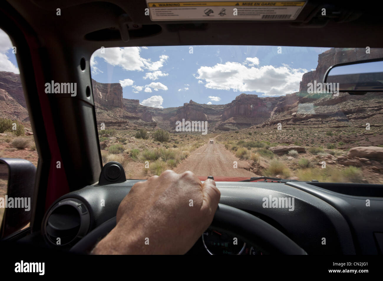 View of Remote Road Across Red Rocks Through Jeep Window, Moab, Utah, USA - Stock Image