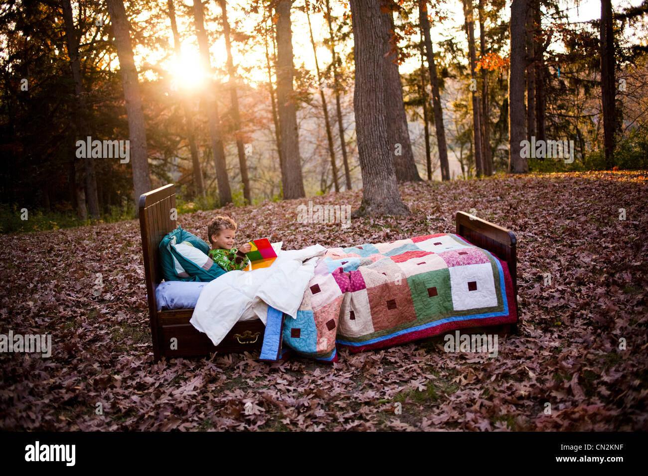 Young boy in bed in forest - Stock Image