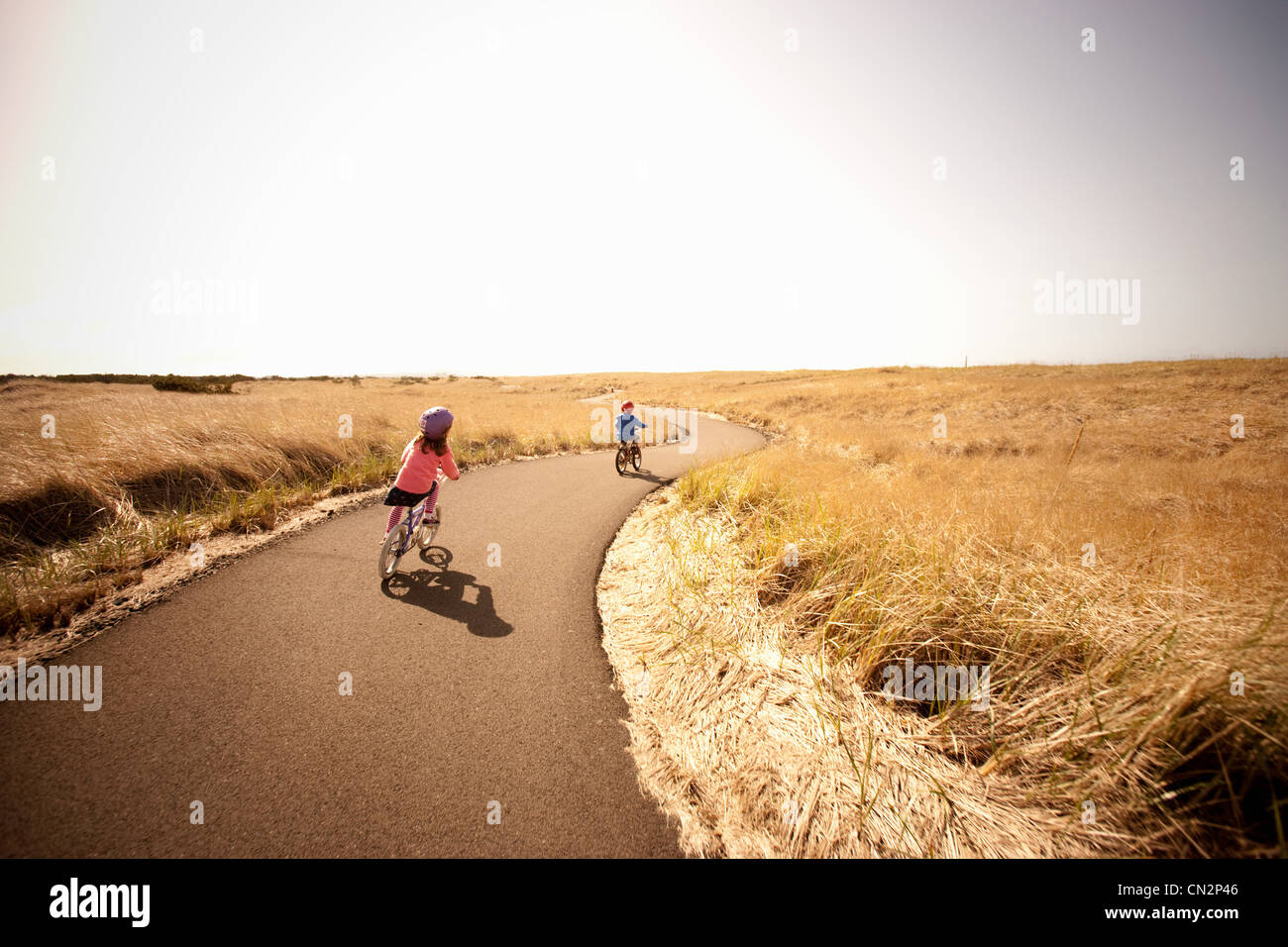 Two children cycling along lane - Stock Image
