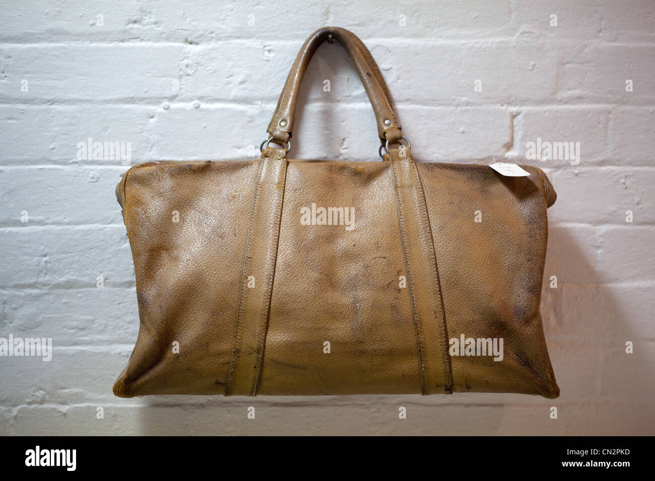 Leather holdall hanging on brick wall - Stock Image