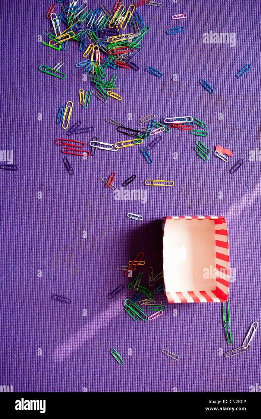 Paper clips on purple carpet - Stock Image