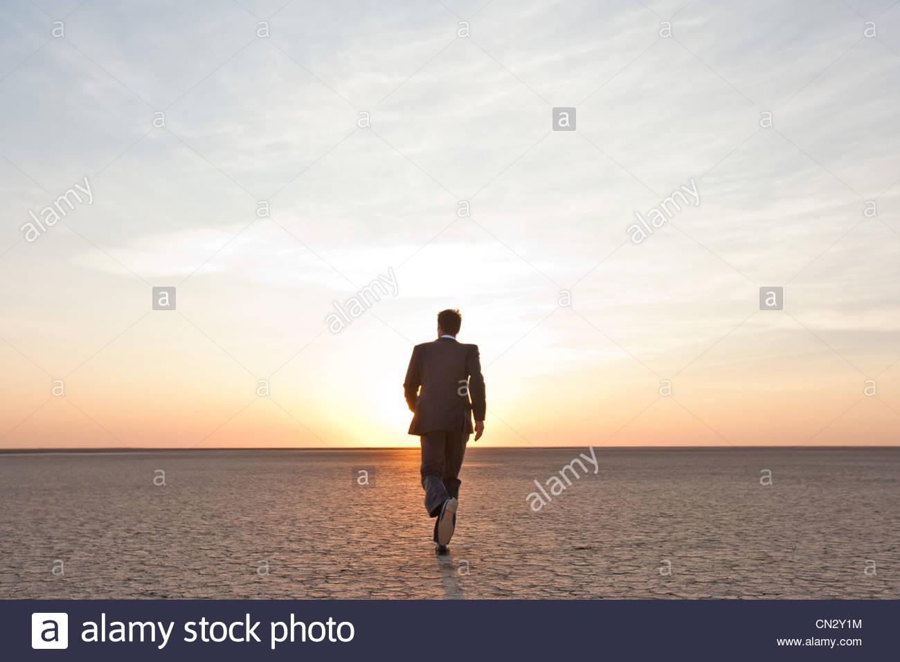 Businessman walking alone in the desert - Stock Image