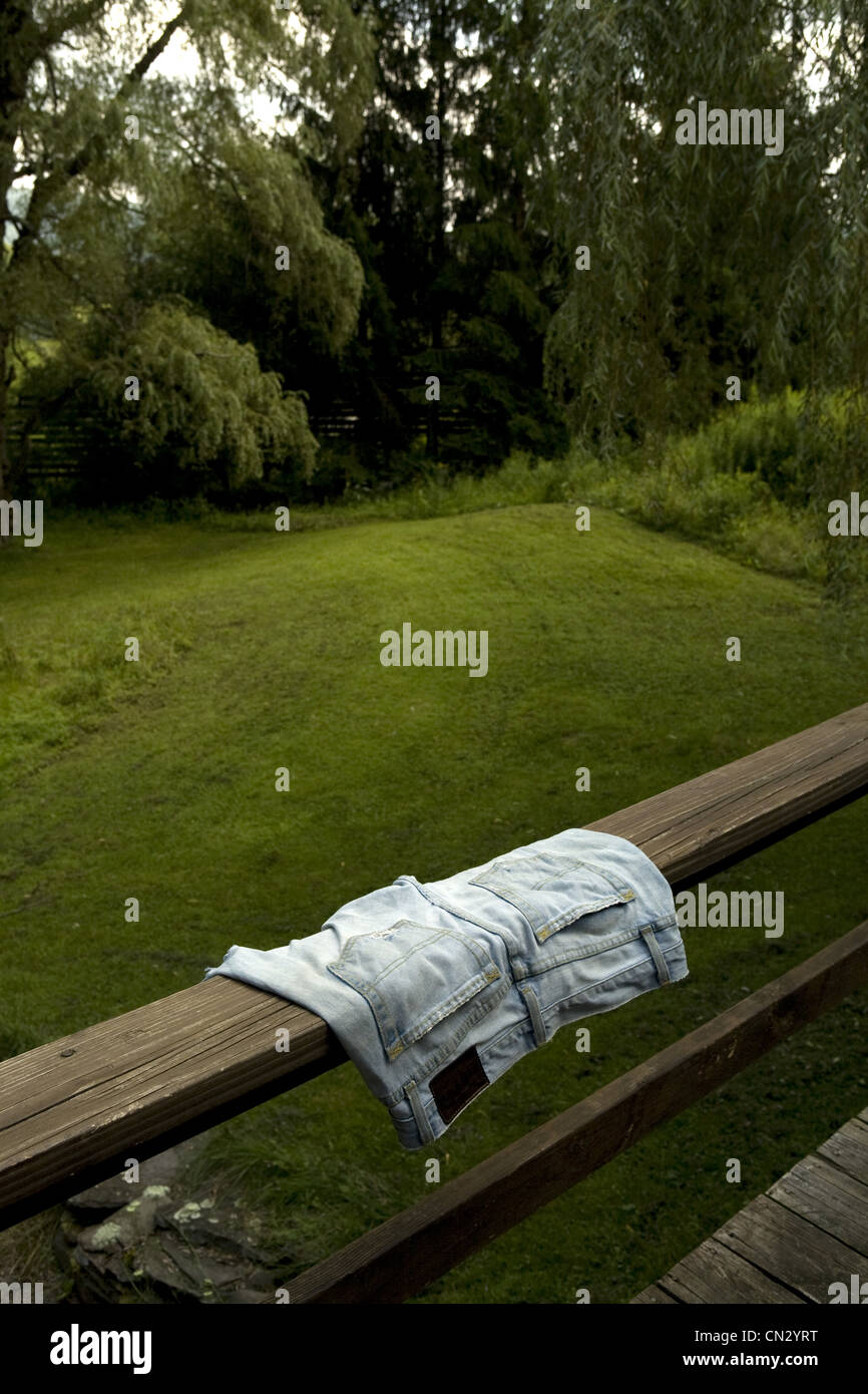 Jean shorts on wooden rail - Stock Image