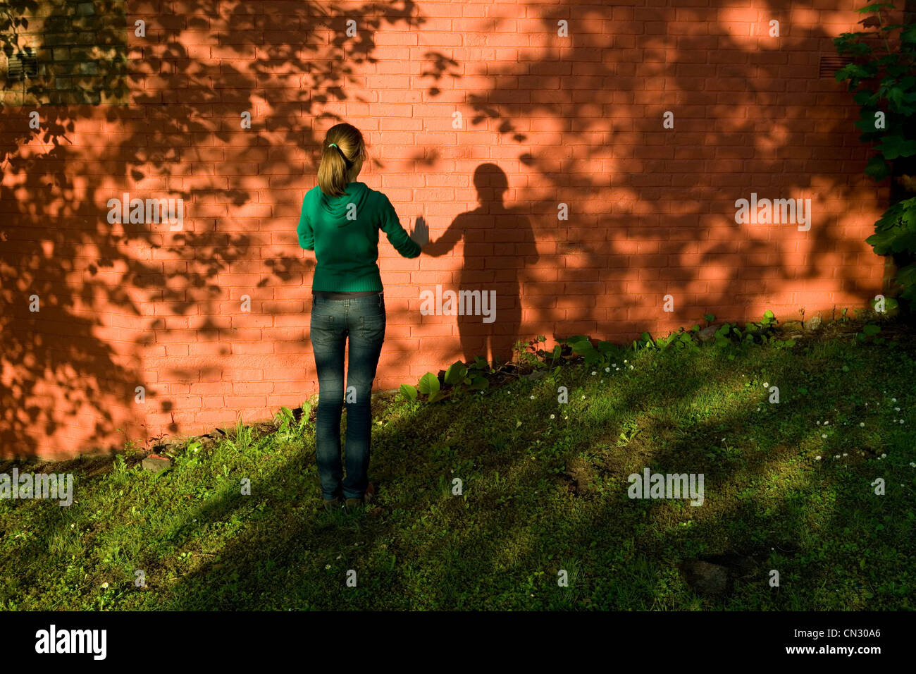 Teenage girl standing by brick wall - Stock Image