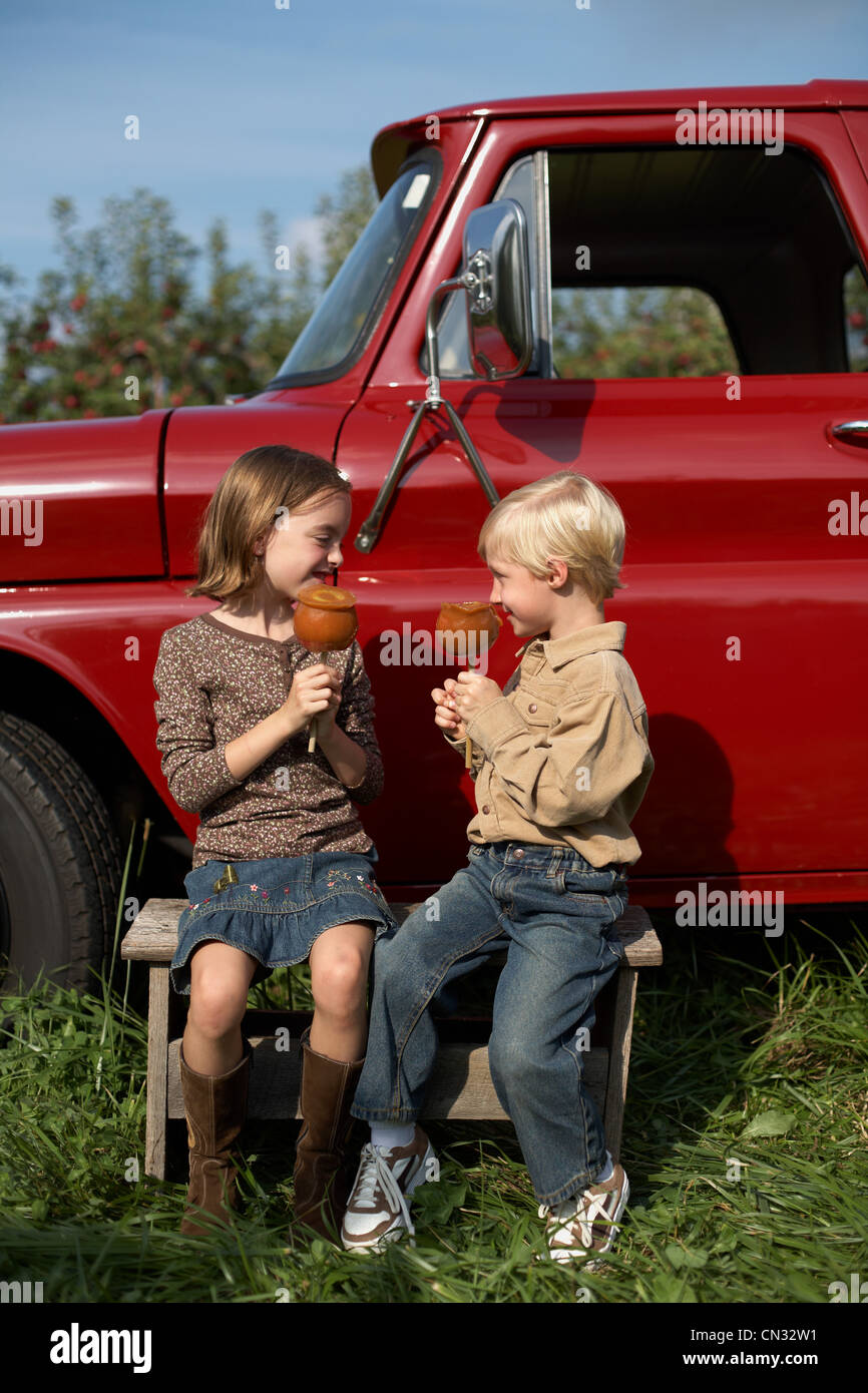 Boy and girl eating toffee apples by truck - Stock Image