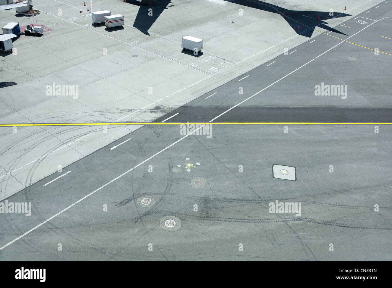 Airport runway with shadow of plane - Stock Image