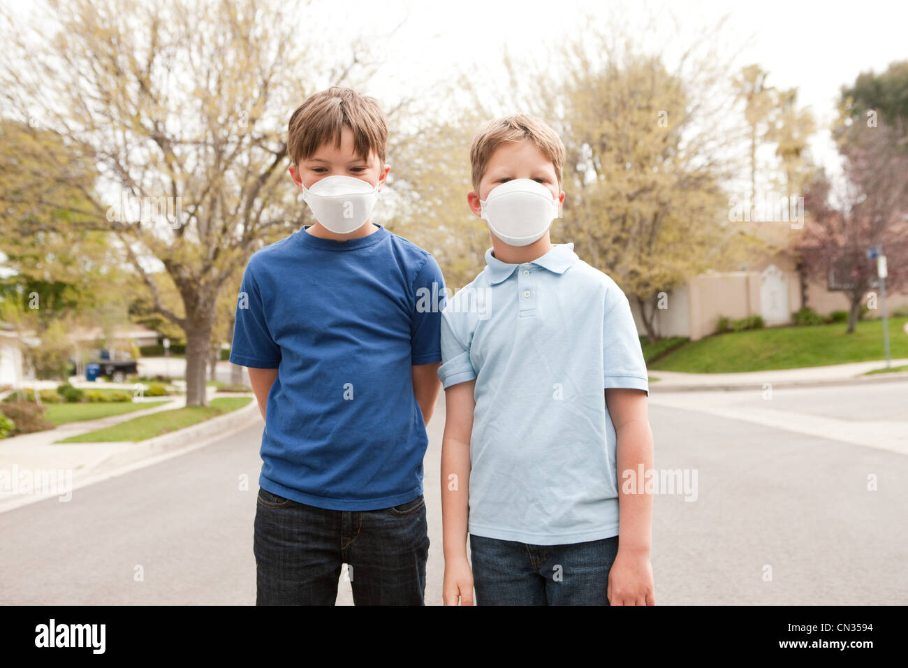 Two boys wearing dust masks - Stock Image
