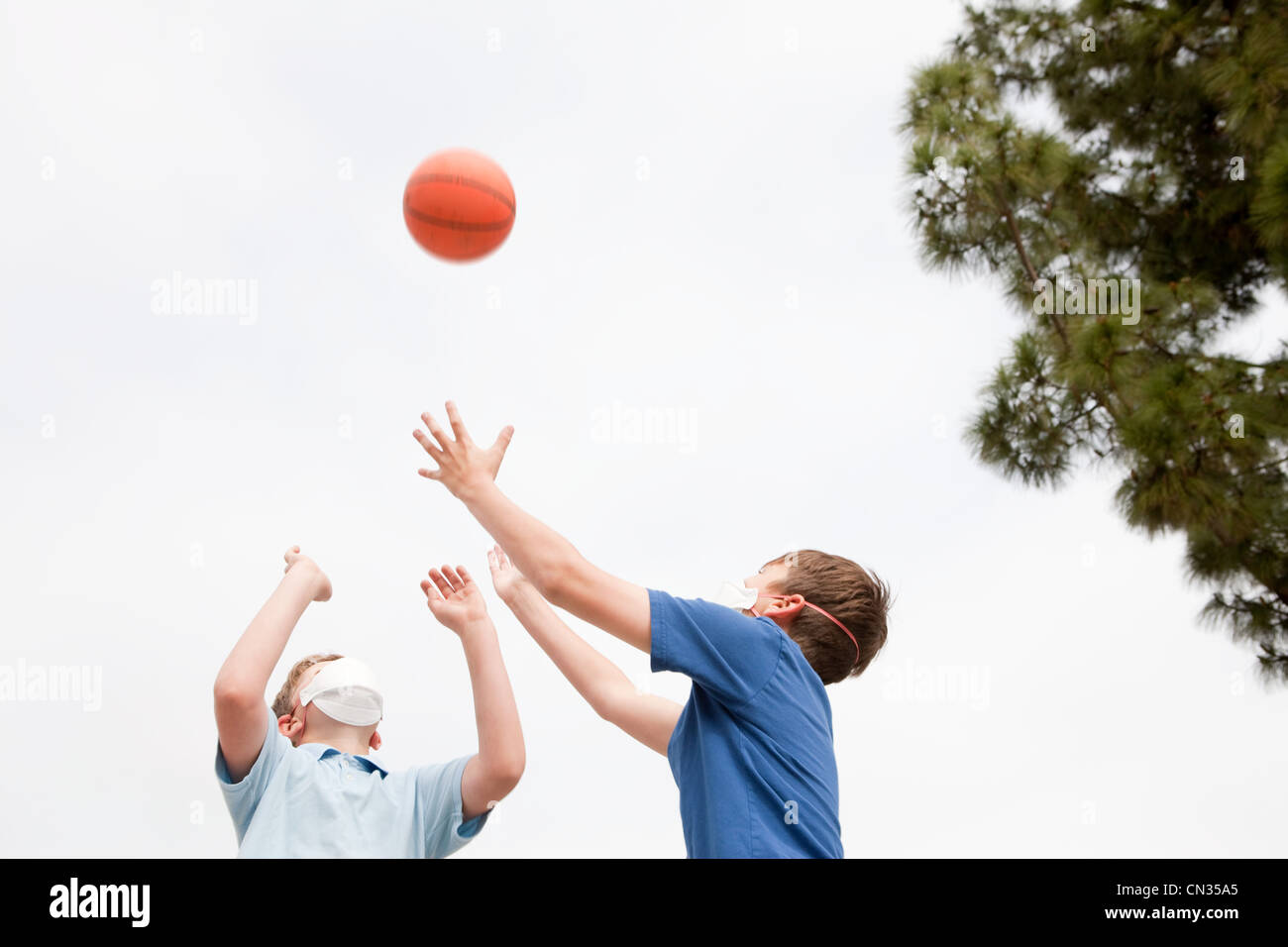 Two boys wearing dust masks playing basketball - Stock Image