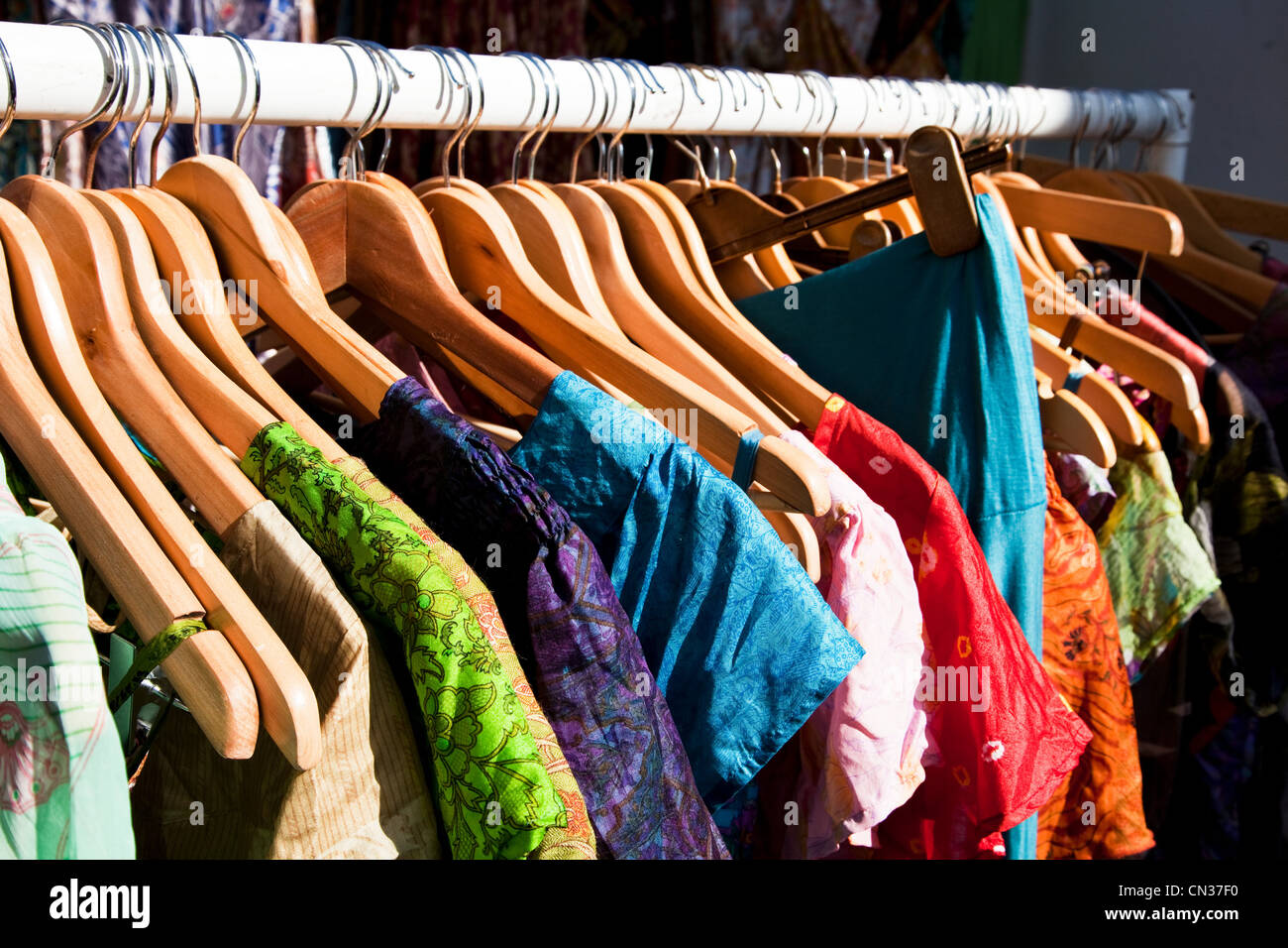 Clothing hanging on clothes rail - Stock Image