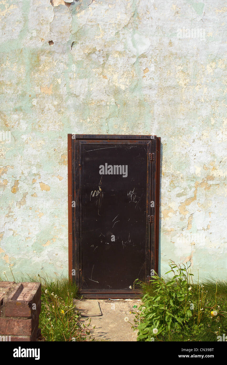 Derelict house with steel door - Stock Image