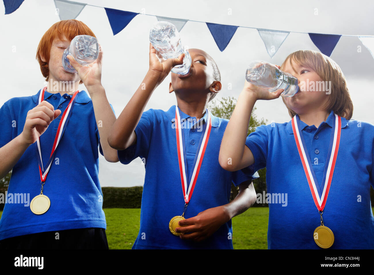 School boys with medals drinking water after sports event - Stock Image