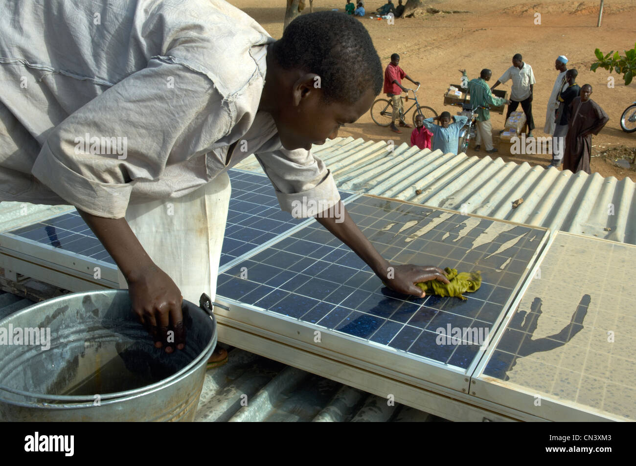 Young boy cleans dust of solar panels in Africa - Stock Image