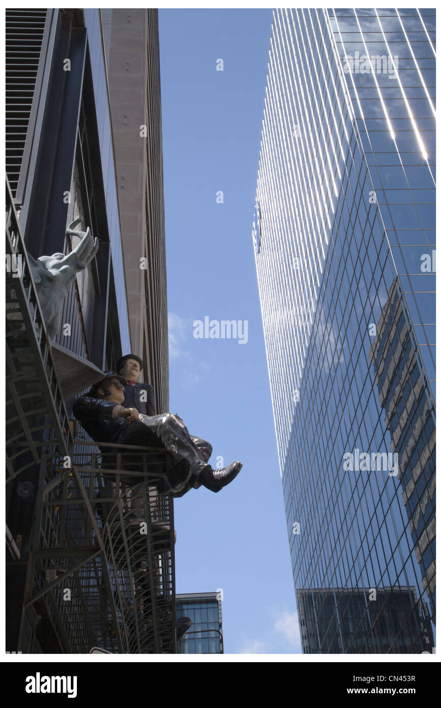 Figurines of man and an elephant perched on a railing on office towers in downtown Montreal, Quebec, Canada - Stock Image