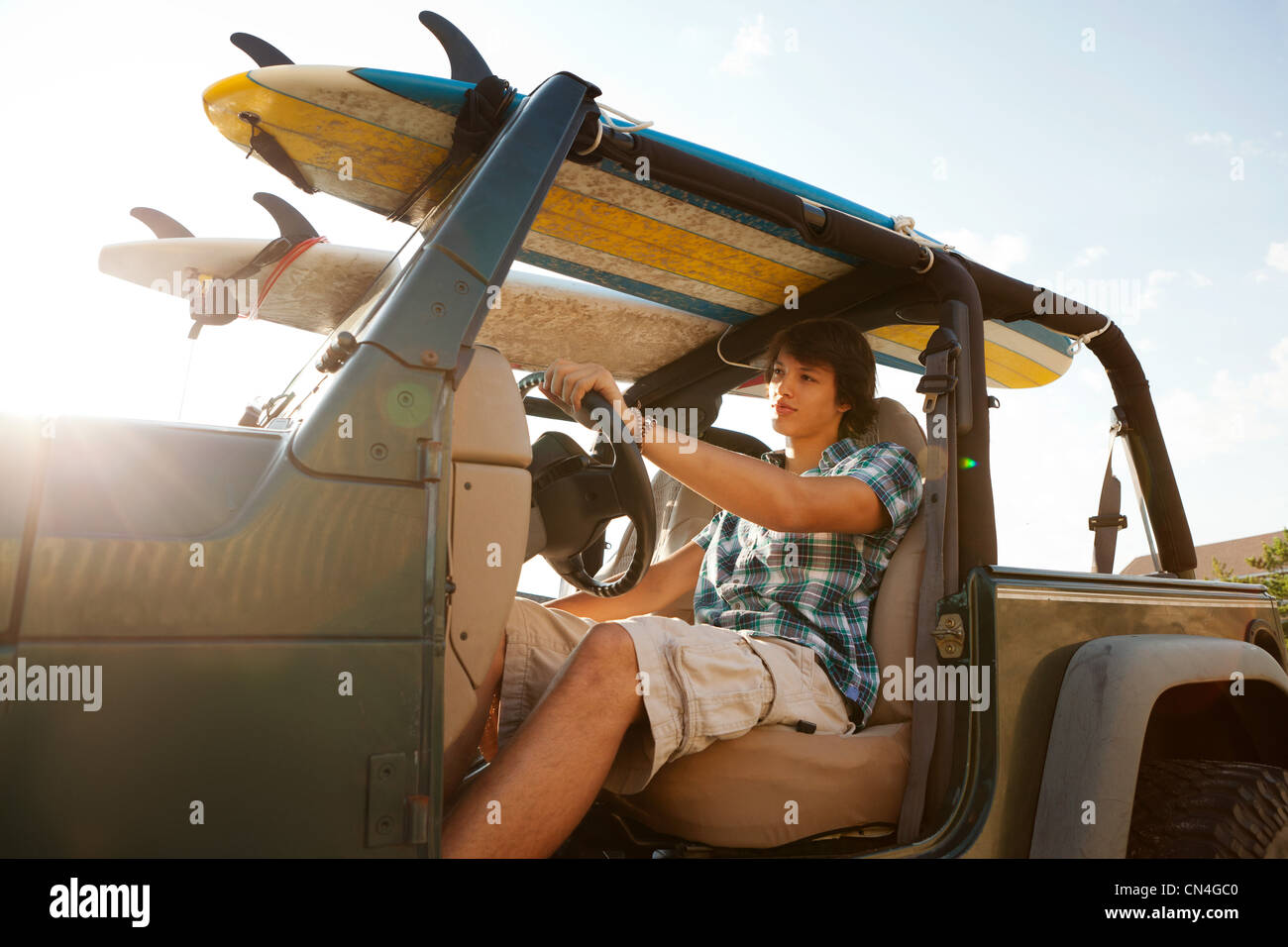 Teenager driving jeep with surfboards - Stock Image