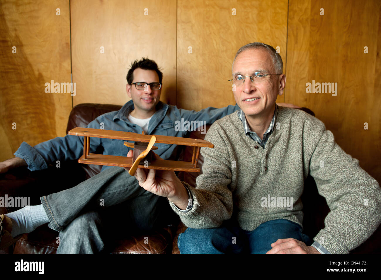 Father holding toy plane with adult son on couch, smiling - Stock Image